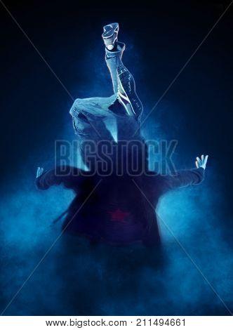 Young man break dancing on dark smoke background. Toned image