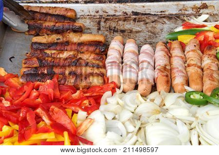 Bacon wrapped hot dogs onions jalapenos and several varieties of bell peppers grilling on an outdoor vendors grill. Close up.