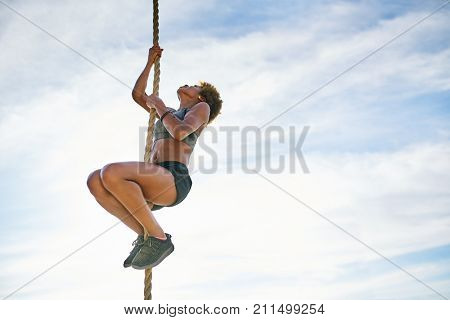 athletic african american woman climbing ropes