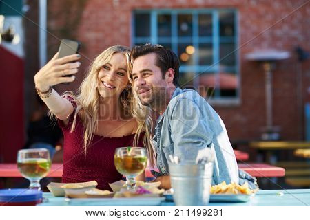 romantic couple taking selfies at mexican taco restaurant