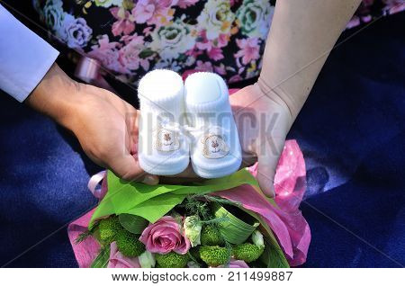 Pregnant woman belly holding baby booties. Newborn baby booties