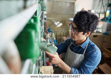 Shoemaking specialist choosing workpiece form of footwear from shelf in workshop