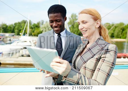 Smiling middle-aged white collar worker and her young African American colleague using digital tablet while standing on upper deck of ship during business trip