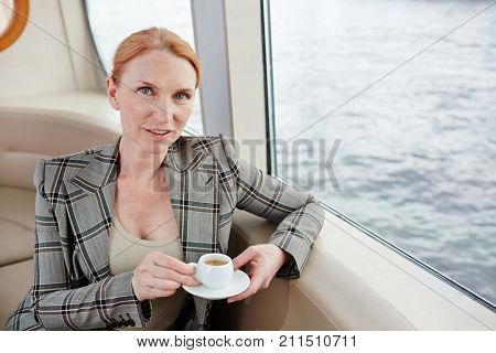 Confident middle-aged entrepreneur looking at camera while sitting at middle deck and enjoying fragrant coffee, waist-up portrait