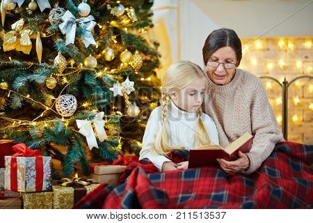 Aged woman reading book of fairy-tales to cute girl by decorated Christmas tree