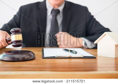 Male Judge lawyer In A Courtroom Striking The Gavel on sounding block in his office.