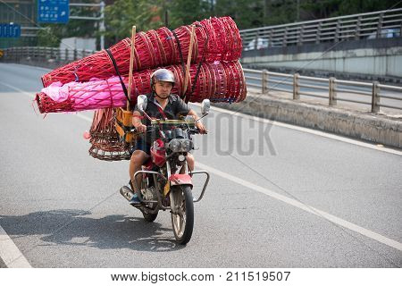 Chengdu, China - July 31, 2017 : Chinese man on motorbike transporting red bamboo cones used to put flowers for inaugurations, Chengdu, Sichuan Province, China
