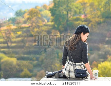 Prague, Czech Republic - October 10, 2017: Pretty Asian girl poses,  looks at the old city of Prague  from observation decks near Prague Castle and holds starbucks coffee, Prague Czech Republic