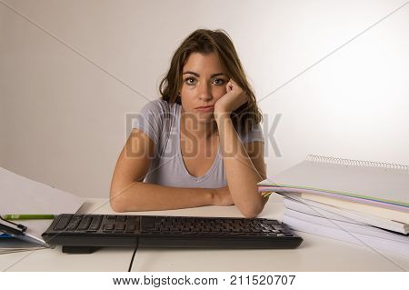 young attractive student girl or working woman sitting at computer desk in stress looking tired exhausted and boring in overwork job and education stress concept isolated clear background