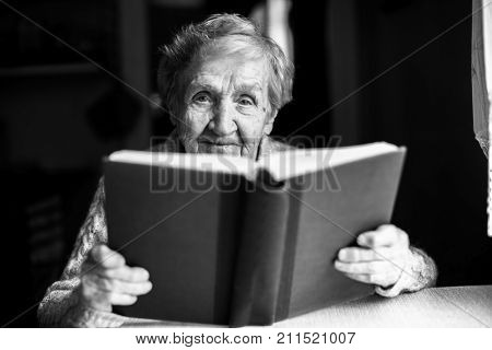 Portrait of elderly woman reading a book. Black-and-white photo.