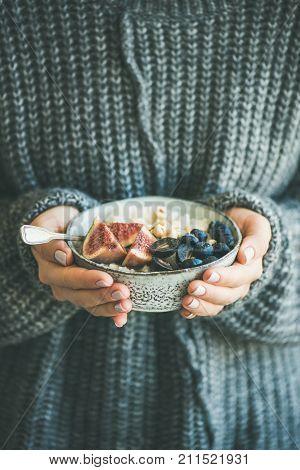 Healthy winter breakfast. Woman in woolen sweater holding bowl of rice coconut porridge with figs, berries, hazelnuts. Clean eating, vegetarian, vegan, alkiline diet food concept