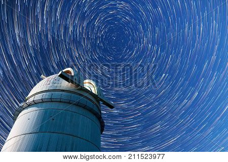 Astronomical observatory under the night sky stars. Blue sky with hundreds of stars of the Milky way. Timelapse in comet mode.