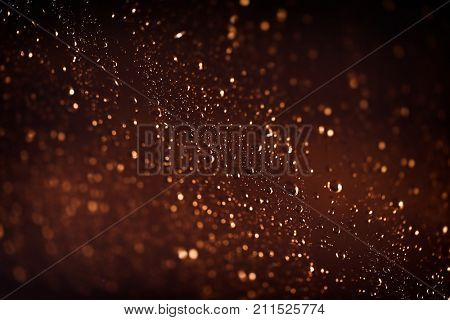 Brown background with water drops, rainy weather at night, rain drops on the window, abstract textured wallpaper, autumn season concept