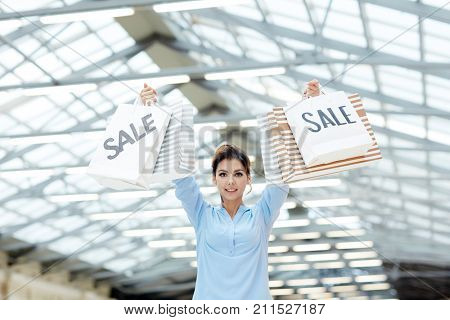 Young woman showing off paperbags with purchases in shopping center