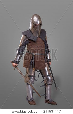 Armored knight in a helmet and with a sword isolated over gray background.