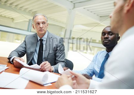 Group of intercultural businessmen discussing new strategies or points of report