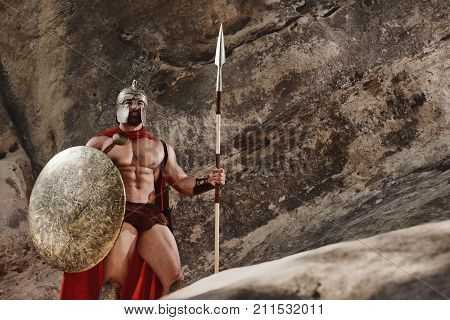 Strong bearded man in helmet and red cloak posing with ancient shield and speak looking away on background of natural rocks.