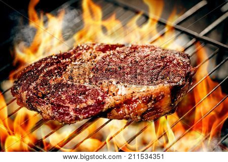 Hot spicy steak grilling on a summer barbecue over the hot coals garnished. Fire Cooking food. close-up