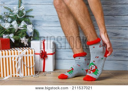Closeup image of a man's legs in woolen socks on a wooden background. Hairy men's legs in New Year's socks. The man straightens his socks with his hands.