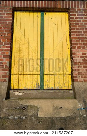 Portal window or door shut with yellow wood planks in derelict building on red brick wall background. Refusing rejecting decay concept