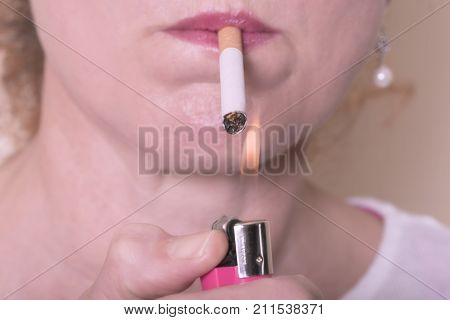 Mature adult woman smoking and lighting  a tobacco cigarette indoors