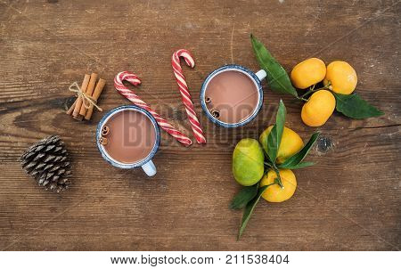 Christmas or New Year attributes. Fresh mandarins with leaves, cinnamon sticks, pine cone, hot chocolate in mugs and candy canes over rustic wooden background, top view