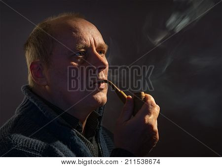 Nice portrait of a Caucasian man with tobacco pipe (low key)
