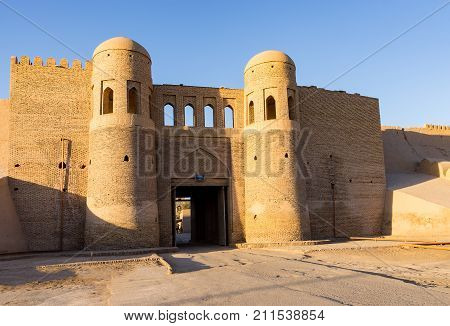 Sunset on twin-turreted western entrance Gate in the ancient city wall of Ichan Kala - Khiva, Uzbekistan