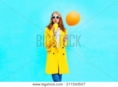 Fashion Pretty Woman Drinks Fruit Juice Holds Orange Air Balloon On A Colorful Blue Background