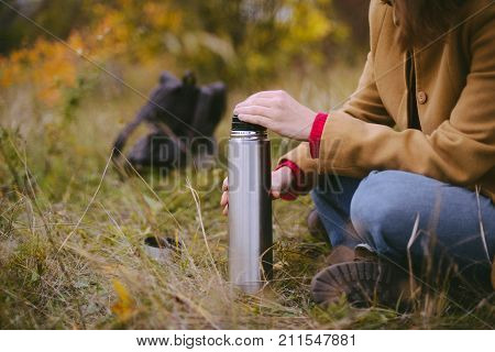 Traveler Girl Pouring Tea From Thermos Cup, Outdoors. Young Woman Drinking Tea At Cup. Theme Travel.
