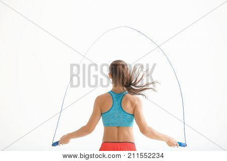 Young woman skipping rope on white background