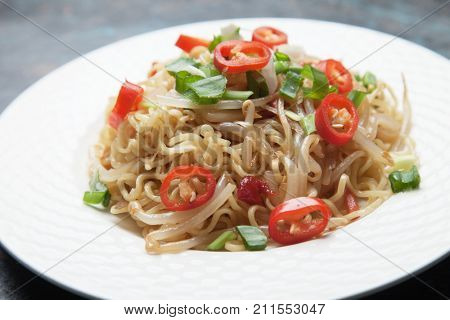 Asian instant noodles with soybean sprouts, spring onion and chili peppers