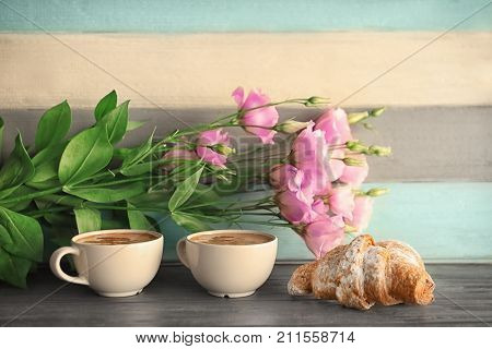 Composition with aromatic morning coffee and beautiful flowers on table