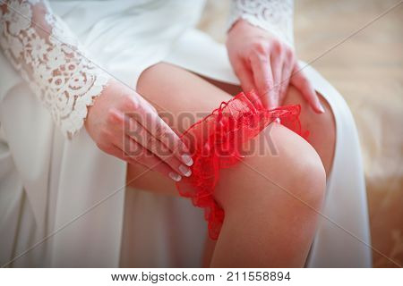 original red bride decoration in the form of a garter on the leg on the wedding day