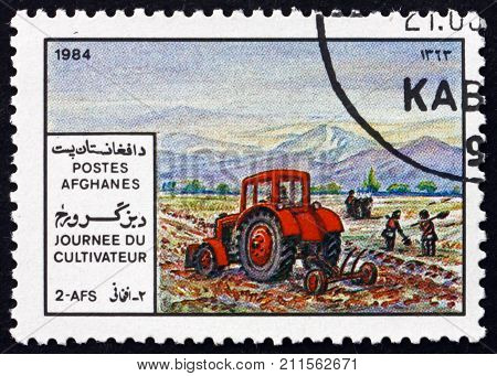 AFGHANISTAN - CIRCA 1984: a stamp printed in Afghanistan shows tractor plowing a field, agricultural scene, farmers day, circa 1984