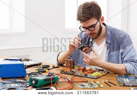 Engineer holding winchester disk in hands. Repairman fixing broken computer hard disk in electronic repair shop, copy space