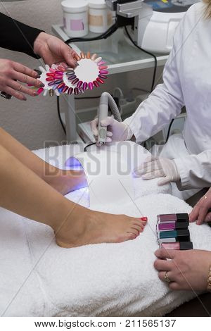 Cosmetologists beauticians in white medical gowns and gloves paint nails on legs of a client with varnish ib different colors on a chair with special equipment in beauty salon. poster