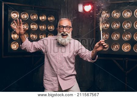 Modern Santa in fashion clothes and in fashionable glasses dancing and have a fun in the club with a sparkle. Happy bearded man on the dark background. Happy Christmas moments. Happy Hew 2018 year!