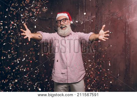 Happy modern Santa wants to hug you! Christmas and New year party with Santa in gold confetti. Modern bearded man in Santa's hat and fashion glasses have a fun and want's to hug all of the children.