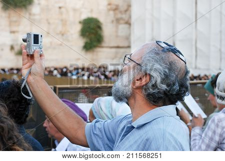 JERUSALEM ISRAEL - JUNE 21 2009: Religious senior jewish man take picture at Western Wall in Jerusalem Israel