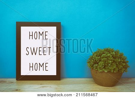 Motivational And Inspirational Life Quotes - Home Sweet Home. Frame And Plant With Teal Blue Backgro
