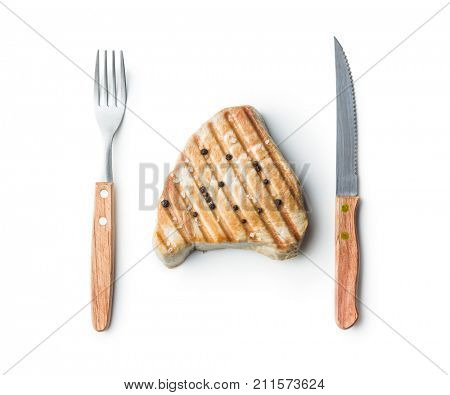 Grilled tuna steak and fork with knife isolated on white background.