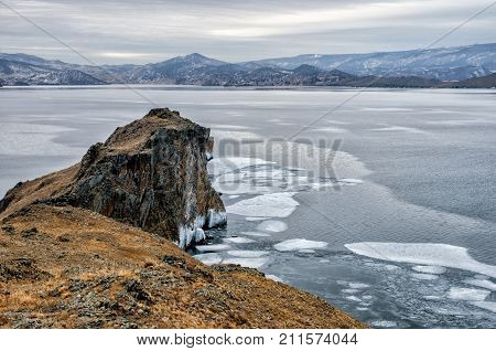 Baikal Lake and rock in the December cold. Time of freeze-up. Ice floes is swiming on the water. Siberia, Russia