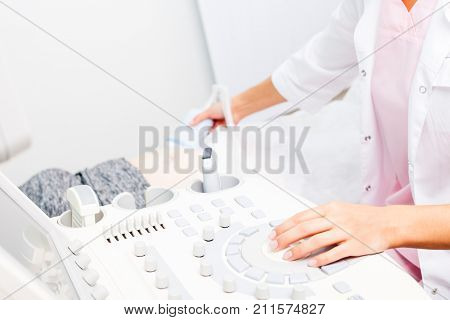 Sonographer operating ultrasound machine while scanning young pregnant woman's belly with ultrasonic transducer doing obstetric ultrasonography poster