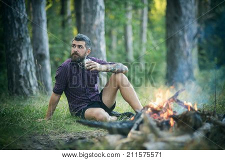 Hipster Hiker With Mug Relax At Bonfire In Forest