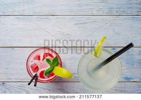 Colorful cocktails. Red Cocktail with ice and lime, Margarita on wooden table top view