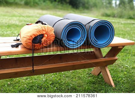 Sleeping pad and tent lie on a wooden bench. Tourist equipment. The concept of tourism, going to the countryside for nature.