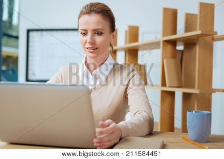 Completely occupied. Close up of attentive secretary using computer while sitting in the office and expressing interest