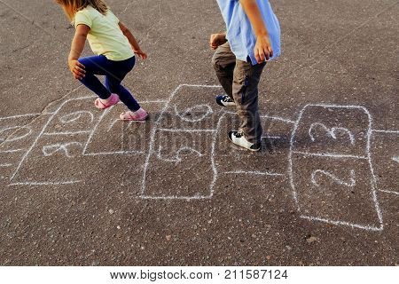 little boy and girl playing hopscotch on playground