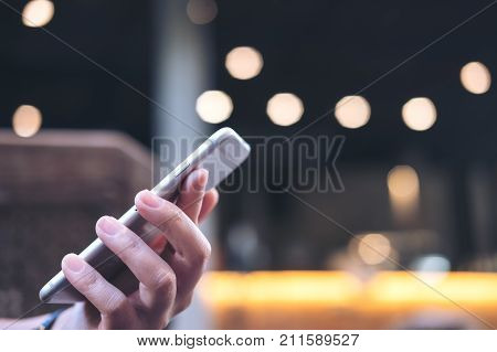 Closeup image of a woman's hand holding and using smart phone in modern cafe